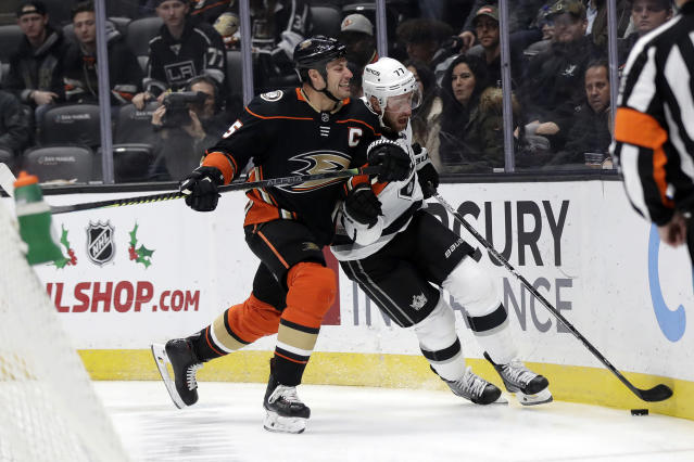 Los Angeles Kings' Jeff Carter, center right, is defended by Anaheim Ducks' Ryan Getzlaf during the first period of an NHL hockey game Monday, Dec. 2, 2019, in Anaheim, Calif. (AP Photo/Marcio Jose Sanchez)