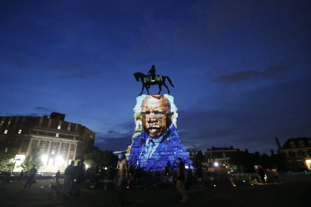 An image of the late Georgia Congressman and civil rights pioneer  John Lewis is projected on to the pedestal of the statue of confederate General Robert E. Lee on Monument Avenue (Steve Helber/AP)
