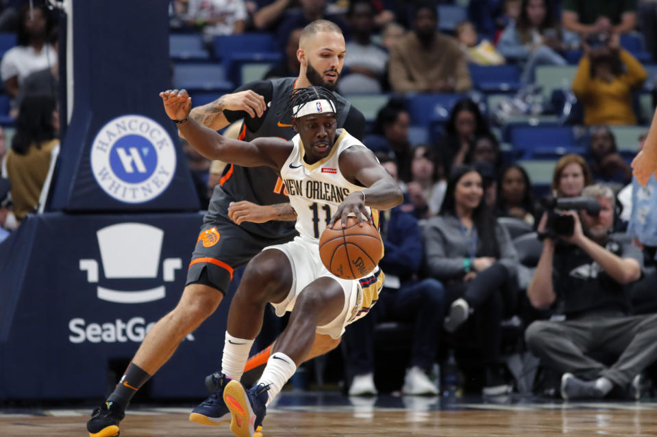 New Orleans Pelicans guard Jrue Holiday (11) dribbles against Orlando Magic guard Evan Fournier in the first half of an NBA basketball game in New Orleans, Sunday, Dec. 15, 2019. (AP Photo/Gerald Herbert)