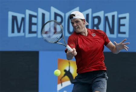Frank Dancevic of Canada hits a return to Benoit Paire of France during their men's singles match at the Australian Open 2014 tennis tournament in Melbourne