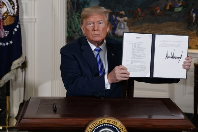 US President Donald Trump shows a signed presidential memorandum after delivering a statement on the Iran nuclear deal at the White House