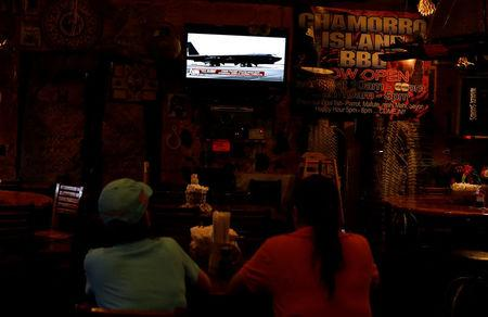 Local residents watch news on North Korea crisis, at a restaurant on Guam