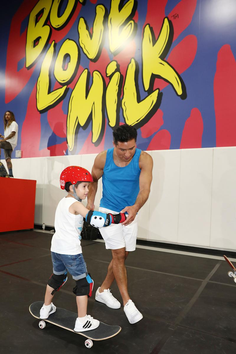 Mario Lopez helps son, Nico, navigate the skate course during an open session at the Bones Love Milk Shredquarters in Huntington Beach, Calif., Wednesday, July 24, 2019. The skatepark is part of a week-long program hosted by the California Milk Processor Board dedicated to celebrating skate and California street culture while showcasing the real benefits of milk as nature's energy drink. (Photo by Matt Sayles/Invision for CMPB/AP Images).