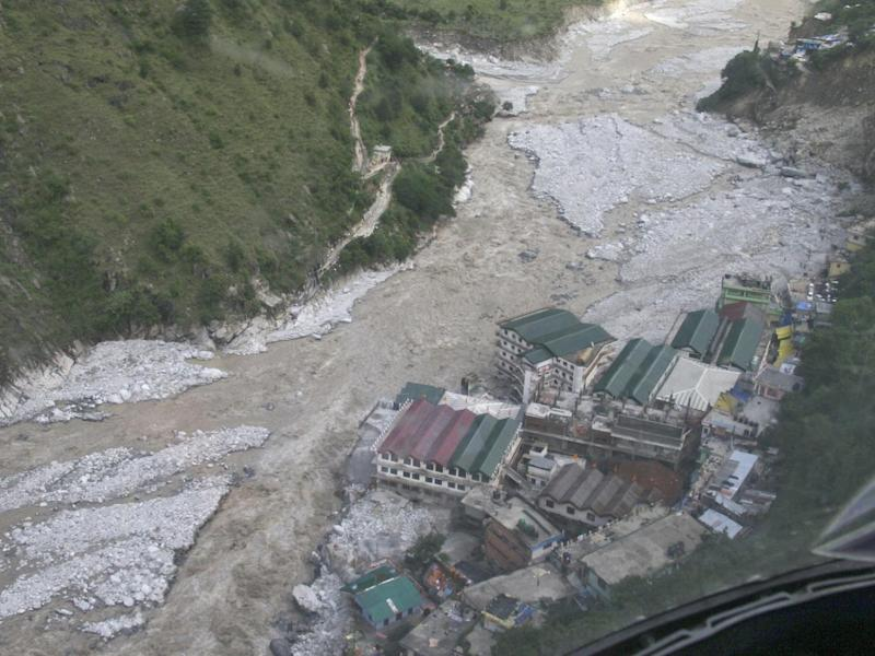 Flood waters flow next to a residential complex during major floods in the Himalayan state of Uttarakhand in 2013 (Reuters)