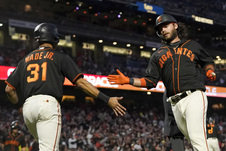 San Francisco Giants' LaMonte Wade Jr., left, celebrates with Brandon Crawford after both scored on a two-run single by Curt Casali during the fourth inning of the team's baseball game against the Atlanta Braves in San Francisco, Saturday, Sept. 18, 2021. (AP Photo/Jeff Chiu)