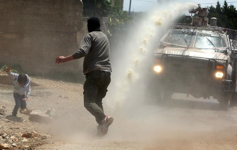 """A Palestinian protester runs to the aid of a boy as an Israeli military vehicle sprays a foul-smelling substance known as """"skunk"""" during clashes in the West Bank village of Kfar Qaddum on May 15, 2015 (AFP Photo/Jaafar Ashtiyeh)"""