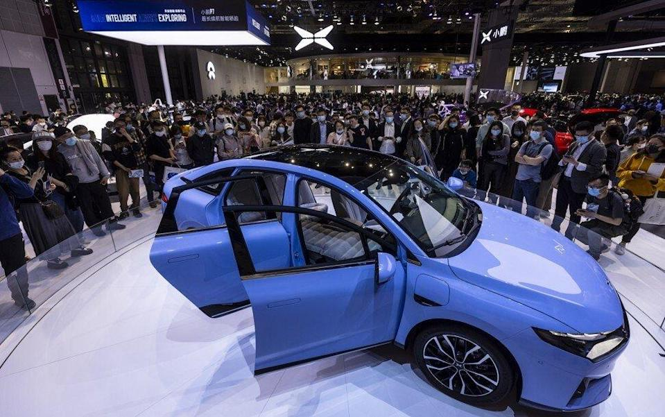 People looking at the P5 car on display at the Xpeng stand during the Auto Shanghai 2021 show in April. Photo: EPA-EFE