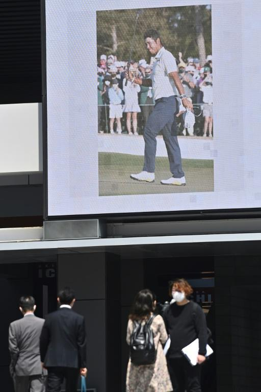 People walk in Tokyo's Akihabara district as a giant screen is emblazoned with news of Hideki Matsuyama's Masters victory. TV networks ran breaking news flashes and several newspapers published special editions