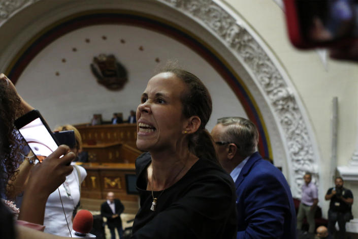 Opposition lawmaker Manuela Bolivar yells against former opposition ally, lawmaker Luis Parra, who is seated at the legislature president's desk, during a session at the National Assembly in Caracas, Venezuela, Tuesday, Jan. 7, 2020. Parra, a former opposition ally, declared himself the National Assembly's leader on Sunday, then today opposition leader Juan Guaidó and opposition lawmakers pushed their way into the legislative building and swore-in Guaido as president of the legislature. (AP Photo/Andrea Hernandez Briceño)