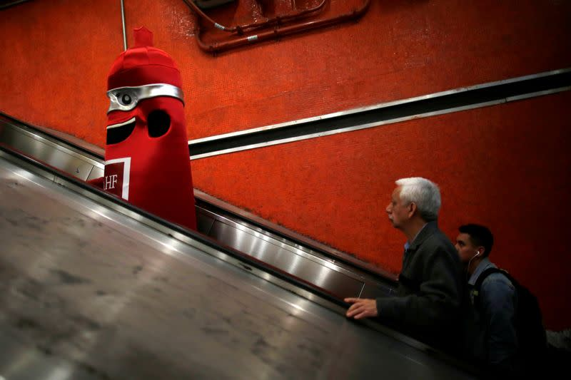 A man wearing a condom costume is seen inside the metro on International Condoms Day, celebrated a day before Valentine Day, in Mexico City