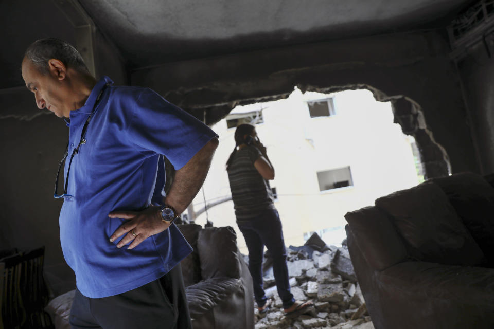 Members of Sror family inspect the damage of their apartment after being hit by a rocket fired from the Gaza Strip overnight, in Petah Tikva, central Israel, Thursday, May 13, 2021. (AP Photo/Oded Balilty)