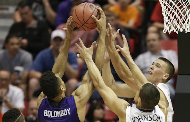 Arizona's Kaleb Tarczewski, right, and Nick Johnson lose the rebound battle with Weber State's Joel Bolomboy during the first half in a second-round game in the NCAA college basketball tournament Friday, March 21, 2014, in San Diego. (AP Photo/Gregory Bull)