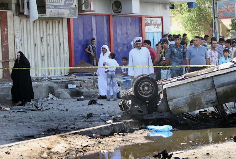 Civilians and security forces inspect the site of a car bomb attack in Basra, 340 miles (550 kilometers) southeast of Baghdad, Iraq, Sunday, Oct. 13, 2013. A string of bombings in mostly Shiite-majority cities across Iraq on Sunday killed and wounded dozens of people, officials said, a grim reminder of the government's failure to stem the uptick in violence that is feeding sectarian tensions in the country.(AP Photo/Nabil al-Jurani)