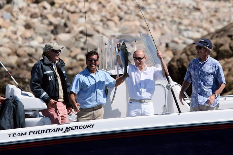 Former President George H.W. Bush (L) and President George W. Bush (R) watch as Russia's President Vladimir Putin holds up his catch, on July 2, 2007, during a morning outing at Walker's Point in Kennebunkport, Maine.