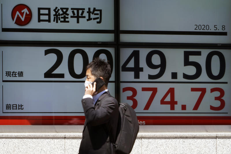 A man wearing a face mask to help curb the spread of the coronavirus walks past an electronic stock board showing Japan's Nikkei 225 index at a securities firm in Tokyo Friday, May 8, 2020. Asian shares surged Friday on optimism the worst of the economic fallout from the pandemic may be over, as Wall Street logged its biggest rally in a week. (AP Photo/Eugene Hoshiko)