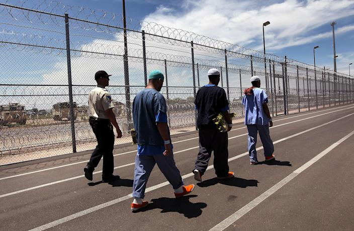 A guard escorts immigrants from Afghanistan, Somalia and Yemen ahead of a Friday Muslim prayer service at the U.S. Immigration and Customs Enforcement (ICE) detention facility in July 2010 in Florence, Arizona. (Photo: John Moore/Getty Images)