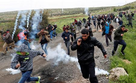 Palestinian demonstrators run from tear gas fired by Israeli troops during a protest marking the Land Day in al-Mughayer village, in the Israeli-occupied West Bank March 29, 2019. REUTERS/Mohamad Torokman