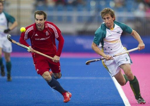 Britain's Nick Catlin (left) and Australia's Simon Orchard run for the ball during a test field hockey match at the Riverbank Arena at the Olympic Park in London on May 5. Anger has given way to excitement as Australia's men's hockey team look to hold all the sport's major titles by winning gold at the London Olympics