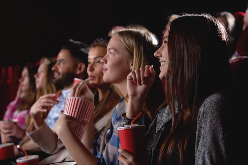 People sitting in a theater with popcorn and drinks.