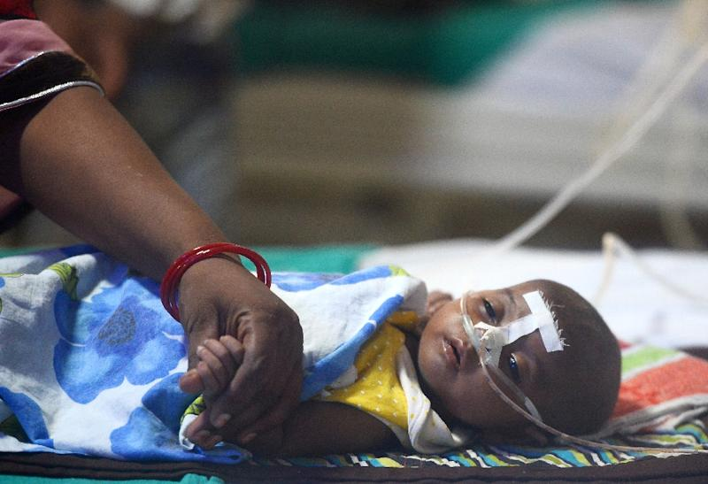 This file photo taken on August 14, 2017 shows an Indian woman holding her child's hand at the encephalitis ward of the Baba Raghav Das Hospital in Gorakhpur, in the northern Indian state of Uttar Pradesh (AFP Photo/SANJAY KANOJIA)