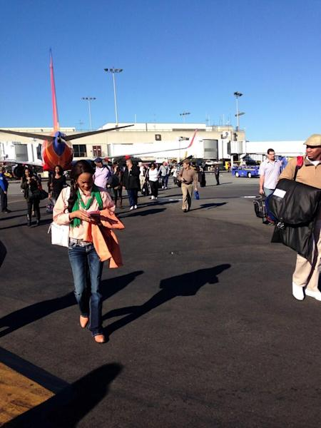 In this photo provided by Natalie Morin, people stand on the tarmac after being evacuated from Los Angeles International Airport, Friday, Nov. 1, 2013, in Los Angeles, after shots were fired at Terminal 3, prompting authorities to evacuate the terminal and stop flights headed for the city from taking off from other airports. (AP Photo/Natalie Morin)