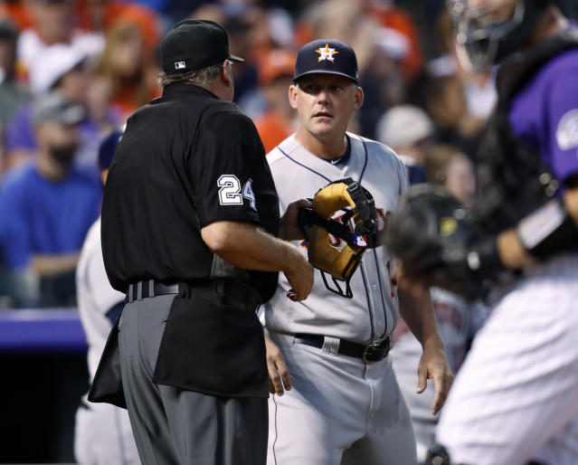 Houston Astros manager AJ Hinch, center, confers with home plate umpire Jerry Layne after a hit by Astros' Alex Bregman was negated by a call of fan interference as Colorado Rockies left fielder Gerardo Parra tried to catch the ball during the sixth inning of a baseball game Wednesday, July 25, 2018, in Denver. (AP Photo/David Zalubowski)