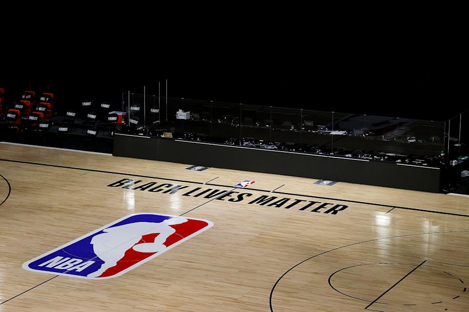 An empty NBA court with Black Lives Matter painted on the floor.