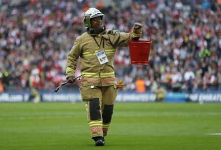 Britain Football Soccer - Arsenal v Manchester City - FA Cup Semi Final - Wembley Stadium - 23/4/17 Fireman removes a smoke bomb from the pitch Action Images via Reuters / Carl Recine Livepic