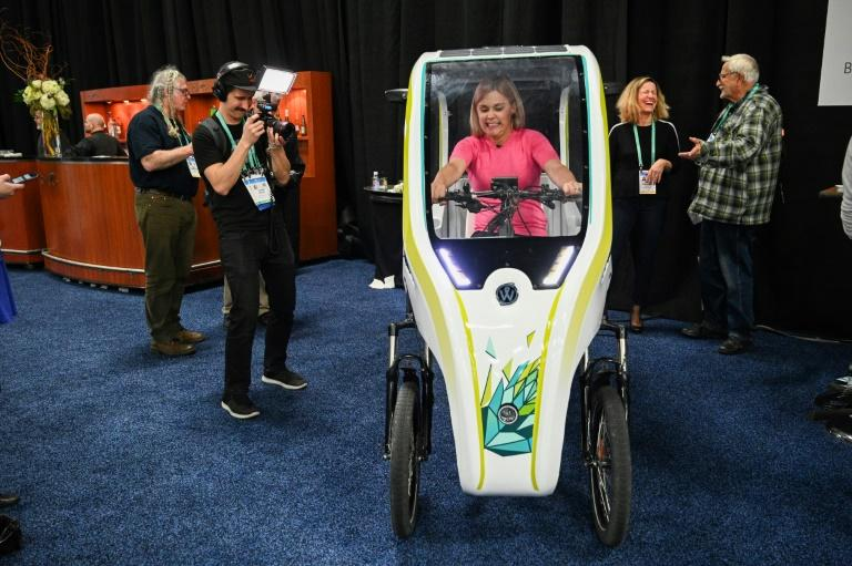 An attendee sits in the Wello solar electric tricycle during the CES Unveiled preview at the 2020 Consumer Electronics Show (AFP Photo/Robyn Beck)