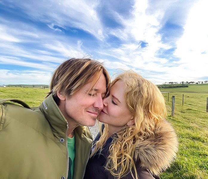 Nicole Kidman kisses husband Keith Urban on the cheek in a grassy field