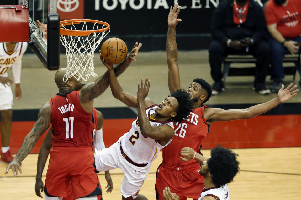 Cleveland Cavaliers guard Collin Sexton (2) puts up a shot between Houston Rockets forward P.J. Tucker (17) and center Justin Patton (26) during the first half of an NBA basketball game Monday, March 1, 2021, in Houston. (AP Photo/Michael Wyke)