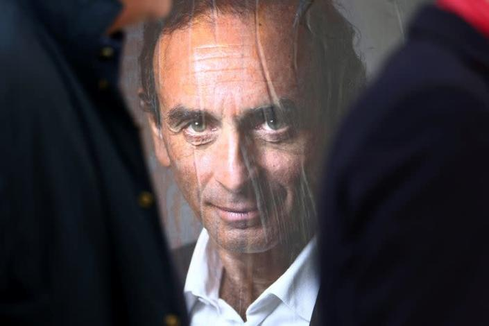 People walk past a poster in support of French far-right commentator Eric Zemmour in Paris