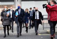 A member of the media points his camera at European Union's chief Brexit negotiator Michel Barnier wearing a face mask as he walks to Brexit trade negotiations in London