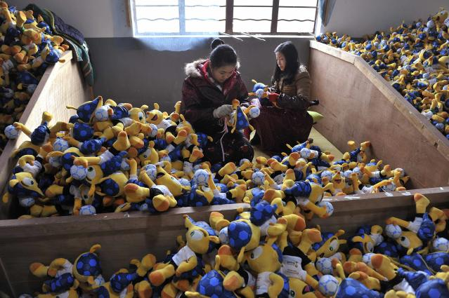 Employees make stuffed toys of Fuleco the Armadillo, the official mascot of the FIFA 2014 World Cup, at a factory in Tianchang, Anhui province January 6, 2014. The 2014 World Cup will be held in Brazil from June 12 through July 13. REUTERS/Stringer (CHINA - Tags: SOCIETY SPORT SOCCER WORLD CUP)