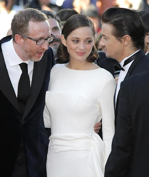 From left, director James Gray, actors Marion Cotillard and Jeremy Renner arrive for the screening of The Immigrant at the 66th international film festival, in Cannes, southern France, Friday, May 24, 2013. (AP Photo/Lionel Cironneau)