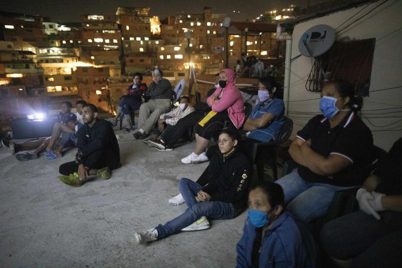 People watch the film Aladdin projected on a screen set up on the roof of a home in the Petare neighborhood of Caracas, Venezuela, late Monday, June 1, 2020. A neighborhood group called The Download Zone set up the movie as a free entertainment option for families cooped up since mid-March under the COVID-19 quarantine. (AP Photo/Ariana Cubillos)