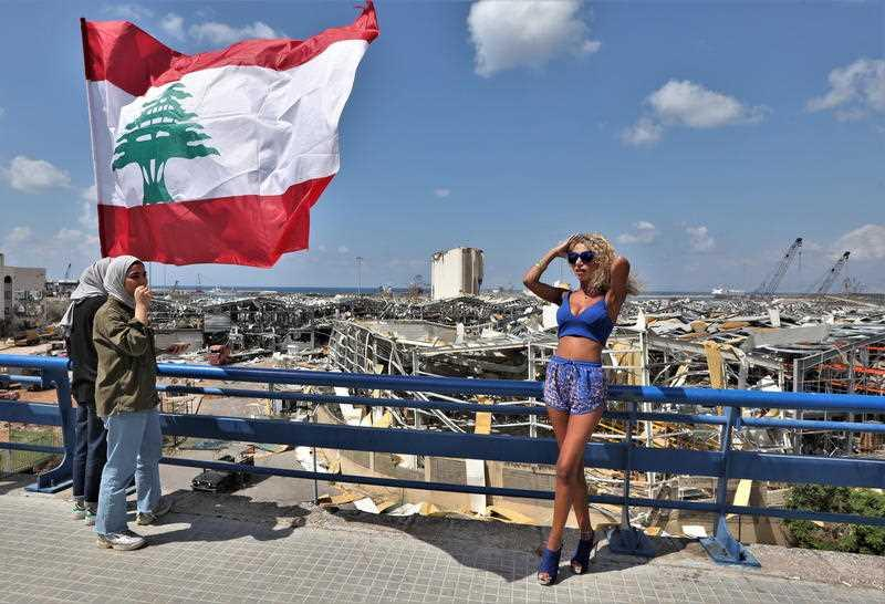 A woman stands next to Lebanese flags on a bridge overlooking the damaged Beirut port and grain silos, in Beirut, Lebanon.