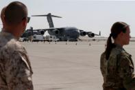U.S. military officers stand near Air Force planes, which were used to evacuate people from Afghanistan, at Al Udeid airbase in Doha
