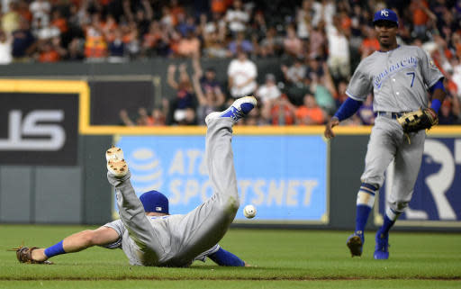 Kansas City Royals first baseman Hunter Dozier, left, can't catch the shallow fly ball hit by Houston Astros' Alex Bregman as right fielder Rosell Herrera watches during the 12th inning of a baseball game, Saturday, June 23, 2018, in Houston. The Royals won 4-3. (AP Photo/Eric Christian Smith)