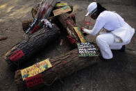 """An activist, attaches posters to logs with messages that read in Portuguese: """"Illegal wood, Amazon lives, Out Salles """" directed at the Environment Minister Ricardo Salles, during a protest against the government's environmental policies, marking World Environment Day, in Brasilia, Brazil, Saturday, June 5, 2021. (AP Photo/Eraldo Peres)"""