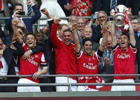 Arsenal's Thomas Vermaelen (R) lifts the trophy as he celebrates with theam mates after winning their FA Cup final against Hull City, at Wembley Stadium in London, May 17, 2014. REUTERS/Eddie Keogh