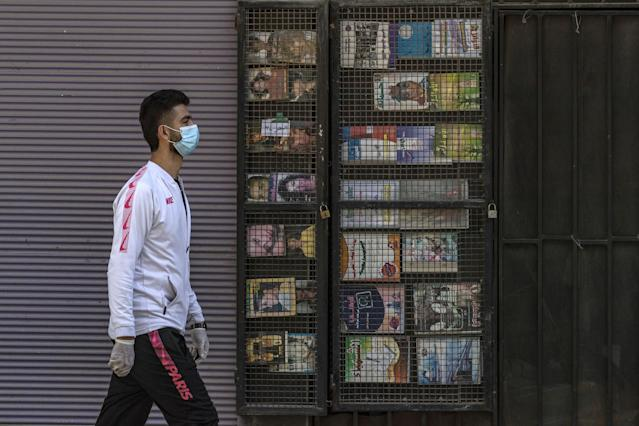 A man is pictured wearing a mask as he walks past closed shops in Qamishli, Syria, on 23 March. Syria has had one confirmed case. (Getty Images)