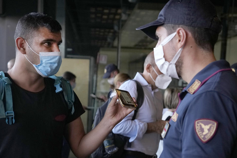 A police officer checks a passenger's phone at Porta Garibaldi train station, in Milan, Italy, Wednesday, Sept. 2, 2021. Italy's government vowed to crack down on demonstrators threatening to block train tracks throughout the country Wednesday as a rule requiring COVID-19 tests or vaccines to use public transportation for long-distance domestic travel took effect. (AP Photo/Luca Bruno)