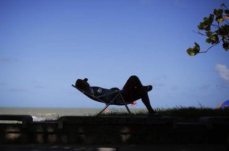 A shop worker rests in the shade along the beach in Recife