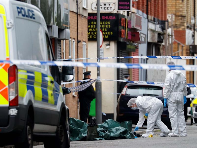 Police officers examine the scene in Toxteth, Liverpool, where a woman was shot by police on 9 July 2020: Phil Noble/Reuters