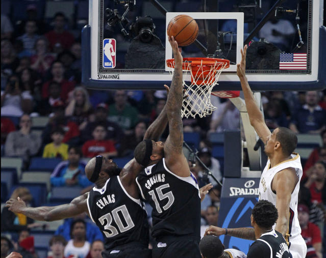 Sacramento Kings center DeMarcus Cousins (15) and forward Reggie Evans (30) leap top blocks a shot by New Orleans Pelicans center Alexis Ajinca in the first half of an NBA basketball game in New Orleans, Monday, March 31, 2014. (AP Photo/Gerald Herbert)