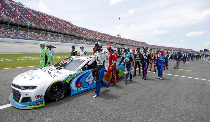 In an extraordinary act of solidarity with NASCAR's only Black driver, dozens of drivers pushed the car belonging to Bubba Wallace to the front of the field before Monday's race as FBI agents nearby tried to find out who left a noose in his garage stall over the weekend. (AP Photo/John Bazemore)