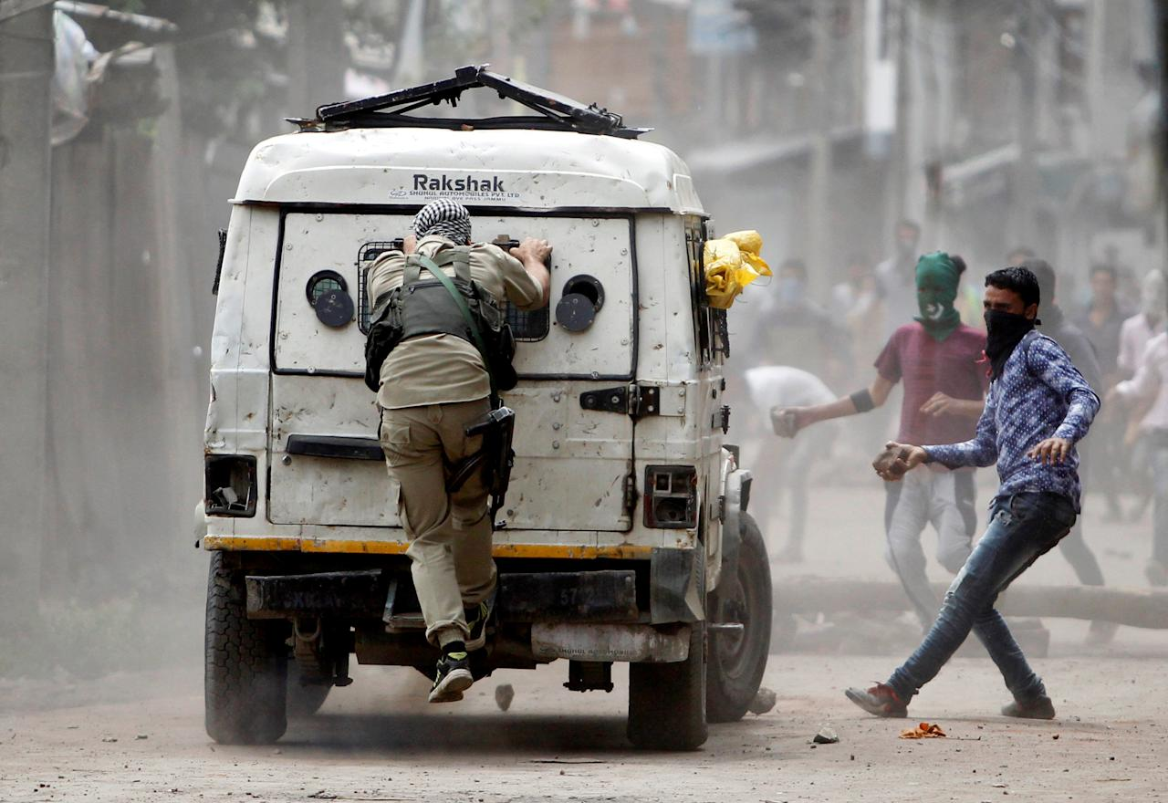 Demonstrators try to hurl stones at an Indian police vehicle during a protest in Srinagar against the recent killings in Kashmir, August 30, 2016.       To match Insight INDIA-KASHMIR/      REUTERS/Danish Ismail/File Photo