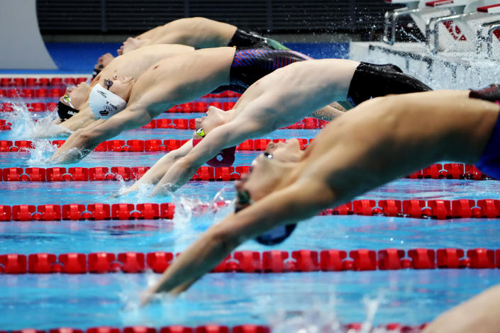 Evgeny Rylov, of Russian Olympic Committee, white cap, dives off the starting block to swim in the men's 200-meter backstroke final at the 2020 Summer Olympics, Friday, July 30, 2021, in Tokyo, Japan. (AP Photo/David Goldman)