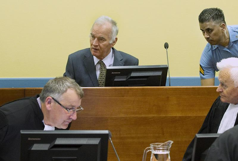 Former Bosnian Serb military commander Gen. Ratko Mladic, center rear, a UN security guard, rear right, and member of his defense, front, are seen at the start of his trial at the Yugoslav war crimes tribunal in The Hague, Netherlands, Wednesday May 16, 2012. Twenty years after the opening shots of the Bosnian War, Mladic has gone on trial on charges of genocide, crimes against humanity and war crimes, his appearance at the UN tribunal marks the end of a long wait for justice to survivors of the 1992-95 war that left some 100,000 people dead. (AP Photo/Toussaint Kluiters, Pool)